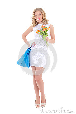 Attractive girl with shopping bags and flowers
