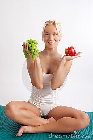 Attractive girl sitting on mat with fruits