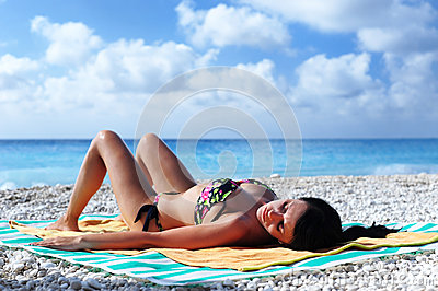Attractive girl sun tanning on a tropical beach