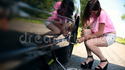 Attractive girl trying to remove wheel with wrench stock footage