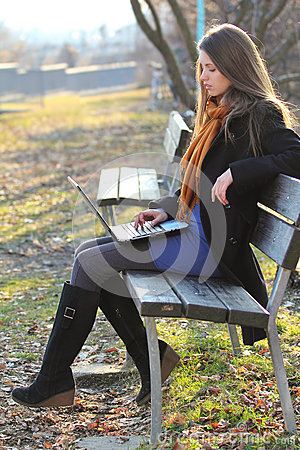 Attractive girl using a laptop computer seated on a bench