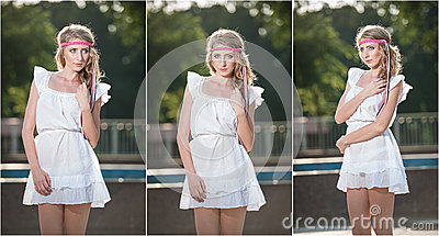 Attractive girl in white short dress sitting near the fountain in the summer hottest day