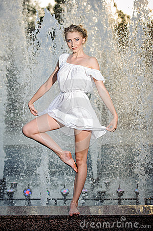 Attractive girl in white short dress sitting on parapet near the fountain in the summer hottest day