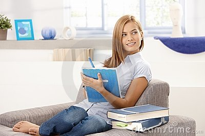 Attractive girl writing notes at home smiling