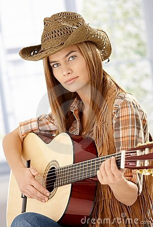 Attractive guitar player practicing in western hat