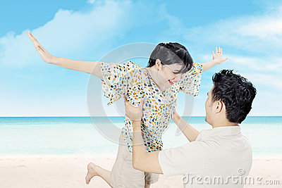 Attractive happy couple have fun on beach