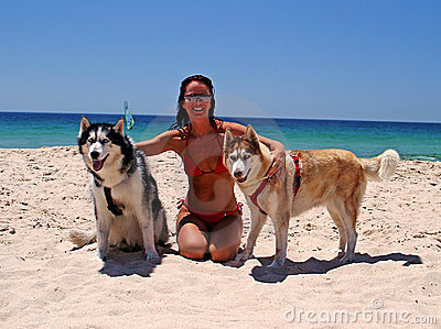 Attractive lady on sunny beach with white sand and blue skies, with two beautiful blue eyed dogs