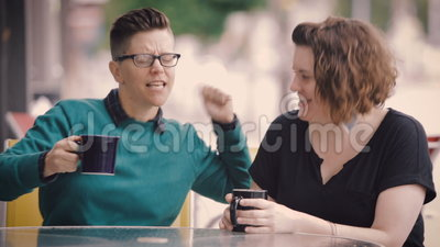 Attractive Lesbian Couple in City. Attractive lesbian couple drink tea in city stock video footage