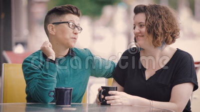 Attractive Lesbian Couple Talk in City. Attractive lesbian couple at coffee shop in City stock video