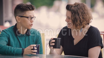 Attractive Lesbian Couple Talk in City. An attractive lesbian couple drink tea and talk in city stock video