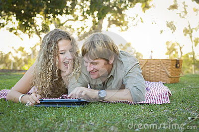 Attractive Loving Couple Using a Touch Pad Outside
