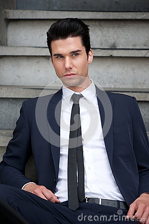 Attractive male fashion model sitting on stairs