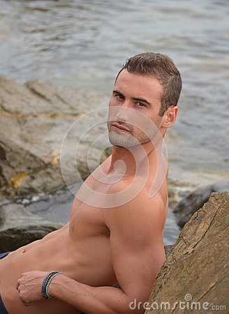 Attractive male model on rock by ocean