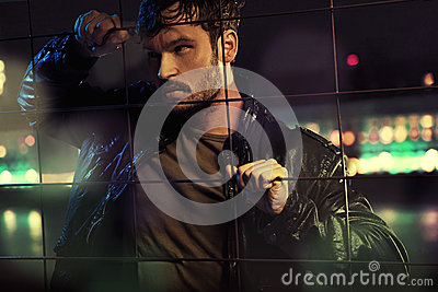 Attractive man behind metal fence