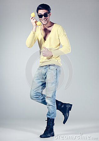 Attractive man smiling talking on a yellow phone