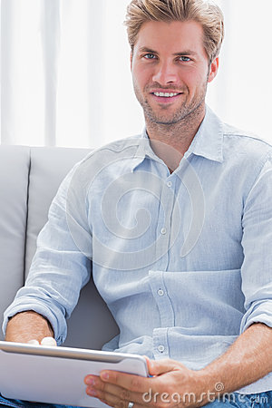 Attractive man using a tablet pc on his couch