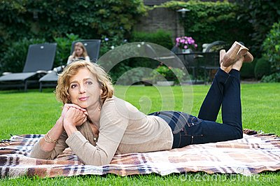 Attractive mature woman relaxing in garden