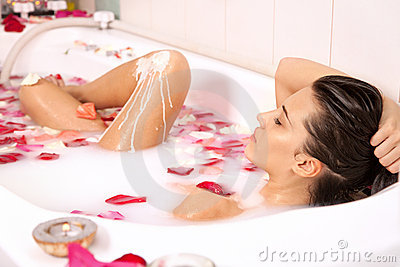 Attractive naked girl enjoys a bath with milk