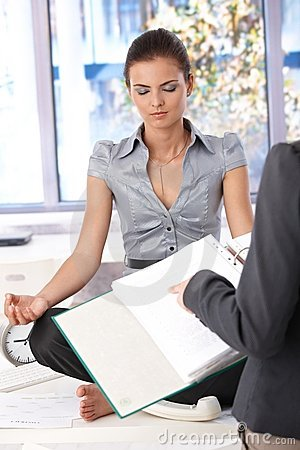 Attractive office worker meditating in office