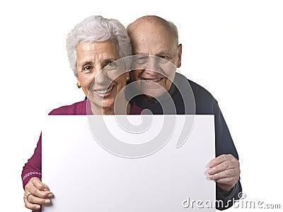 Attractive older couple holding blank billboard