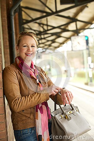 Free Attractive Older Woman Smiling And Pointing To Her Watch Royalty Free Stock Photography - 30598767