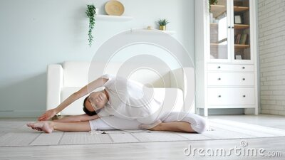 pregnant lady does janu sirsasana sitting on floor near