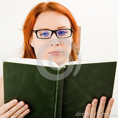 Attractive red-haired girl in glasses reads book.