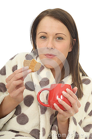 Free Attractive Relaxed Cosy Happy Young Woman Eating Biscuits And Drinking Tea Stock Image - 54157041