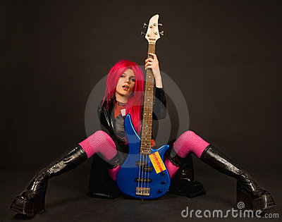 Attractive rock girl sitting with bass guitar