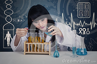 Attractive scientist examining liquid on digital