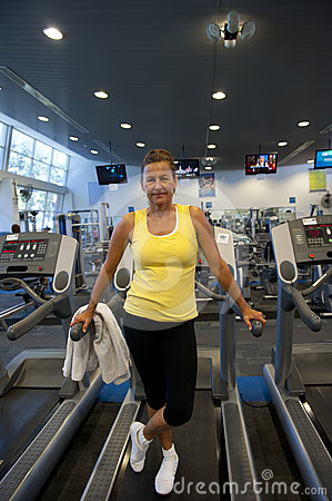 Attractive senior woman exercising at gym