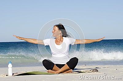 Attractive senior woman meditating at beach