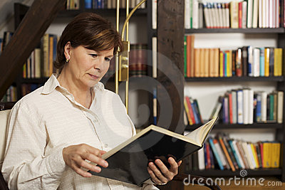 Attractive senior woman sitting and reading a book