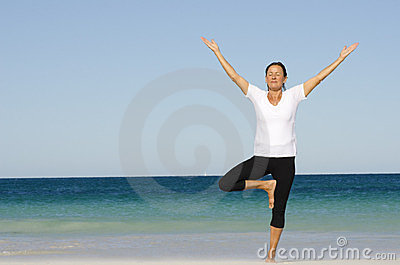 Attractive senior woman stretching at beach