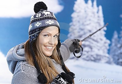 Attractive skier taking a break on top smiling