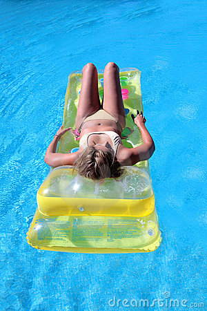 Attractive, slim young lady lying on inflatable sunbed on swimmi