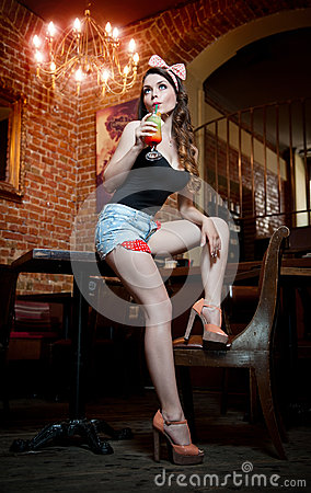 Free Attractive Smiling Pinup Woman In Denim Shorts Sitting On Bar Stool And Drinking Lemonade Royalty Free Stock Photography - 32469717