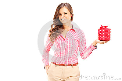 Attractive smiling woman holding a gift box and posing