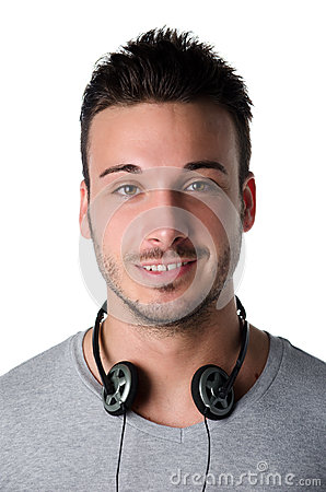 Attractive smiling young man with headphones around his neck