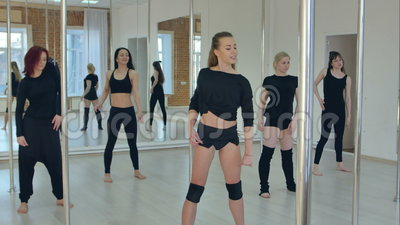 Attractive sport girls stretching before pole dance class in gym with windows. Professional shot in 4K resolution. 087. You can use it e.g. in your commercial stock video