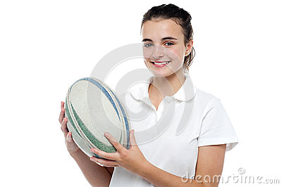 Attractive sporty girl posing with rugby ball