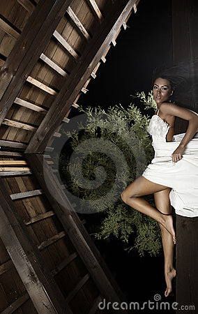 Attractive suntanned girl in white dress poses.