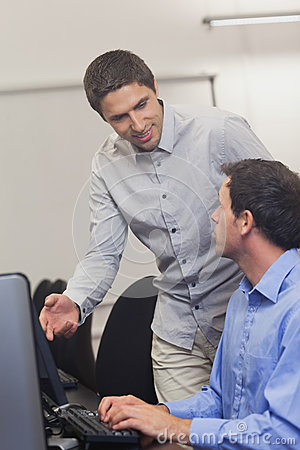 Attractive teacher talking to his student in computer class