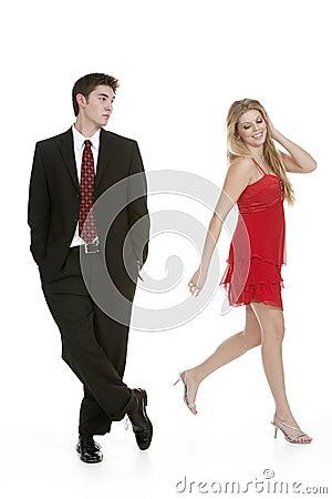 A Boy Walking Away From A Girl ... teenage girl in a red dress walking away from teenage boy in a suit