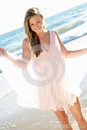 Attractive Teenage Girl Wearing Dress On Beach