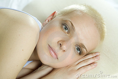 Attractive thoughtful blond bald woman lying