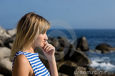 Attractive thoughtful girl rocky beach by the sea.