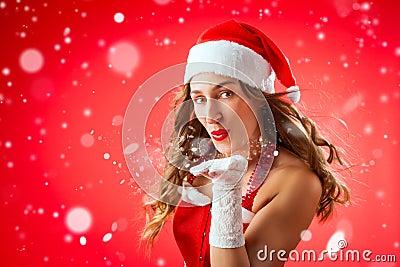 Attractive woman as Santa Claus blowing snow