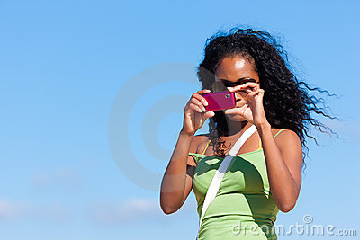Attractive woman at the beach taking picture