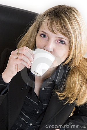 An attractive woman in a black suit drinking a cup of coffee